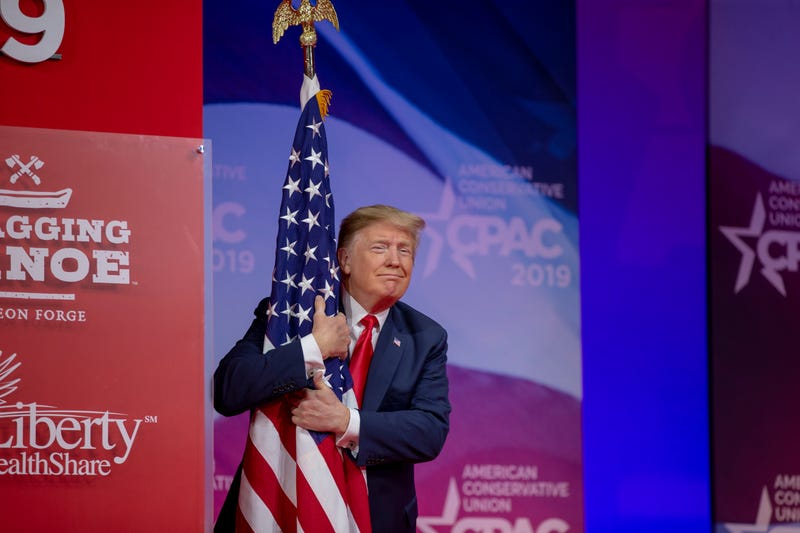U.S. President Donald Trump hugs the U.S. flag during CPAC 2019 on March 02, 2019 in National Harbor, Maryland