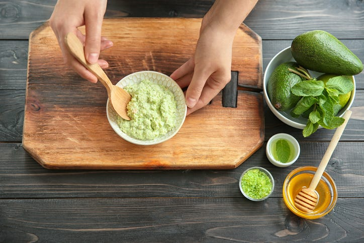woman making avocado and honey face mask