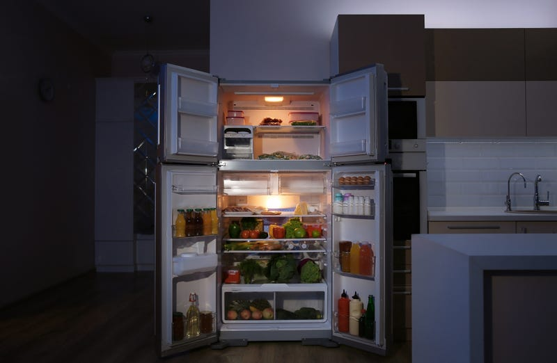 An open fridge at night with the light on