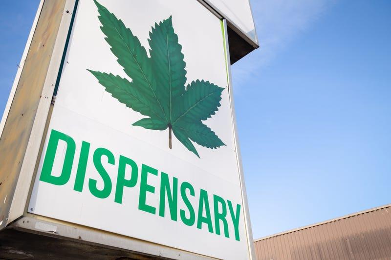 A cannabis dispensary sign with a large marijuana leaf on it