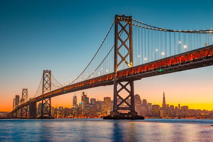 San Francisco skyline with Oakland Bay Bridge at sunset, California