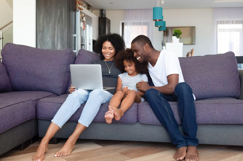 Parents and a daughter sit with a laptop on a couch
