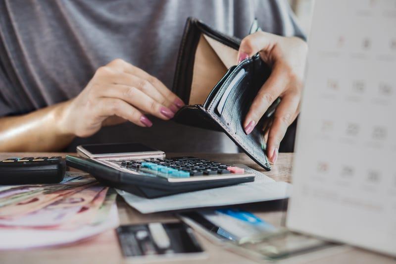 woman looks in empty wallet