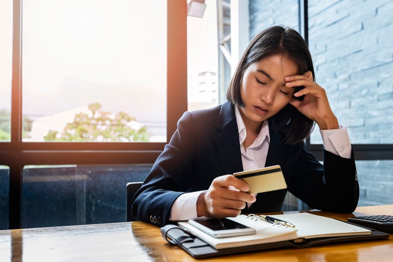 A woman looking anxious with a credit card and bills