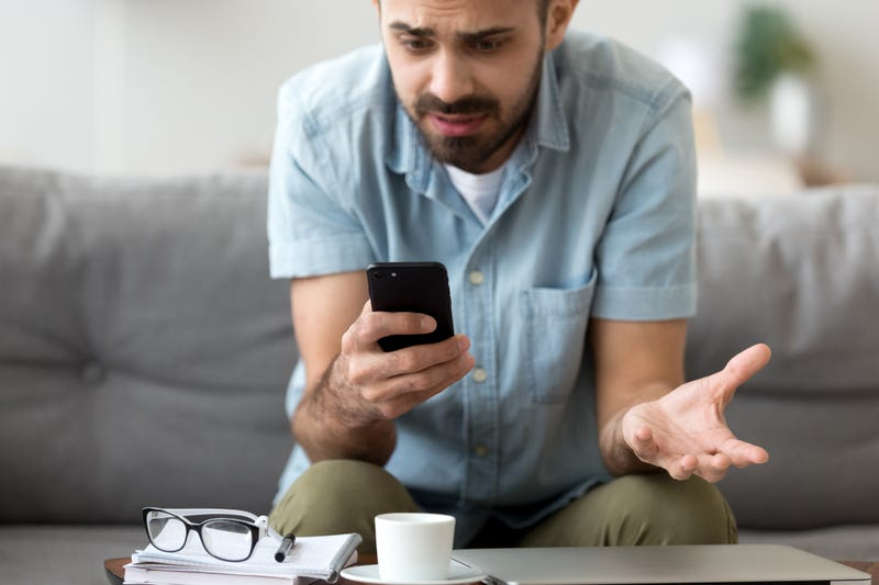 A man looks confused at his phone