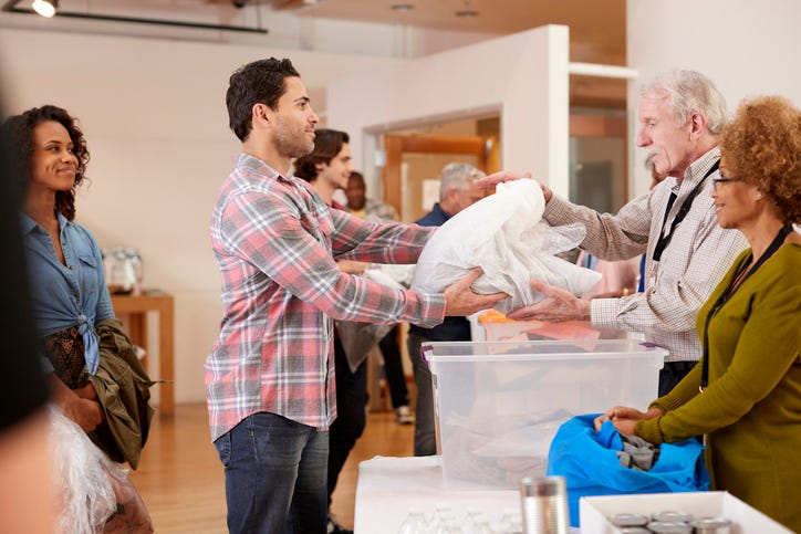A man hands over a stack of clothes to a volunteer