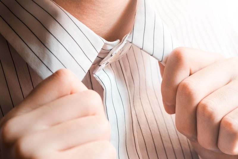 A man's hands adjust the collar of a button-up shirt