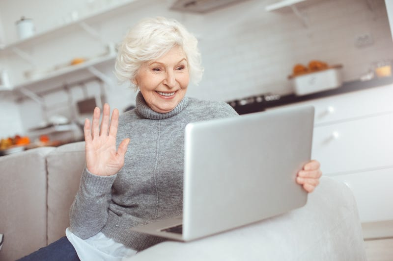 An old woman smiles and waves at her laptop screen