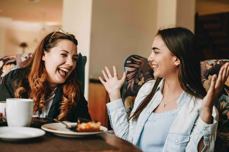 Two women sit at a restaurant table, one making the other laugh with a story