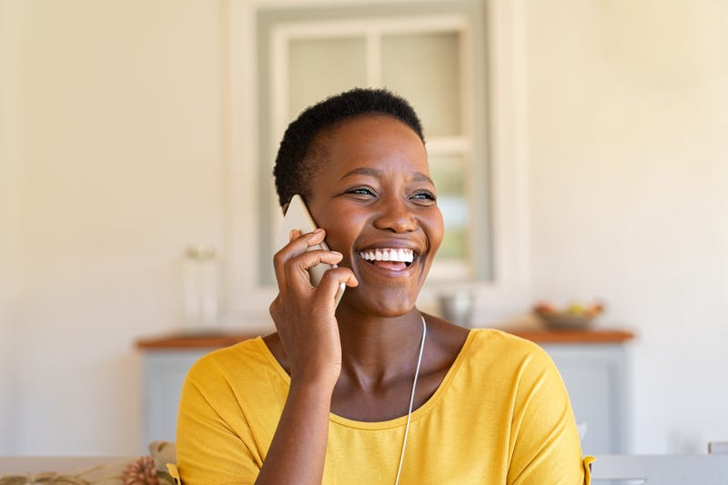 A woman laughs on the phone