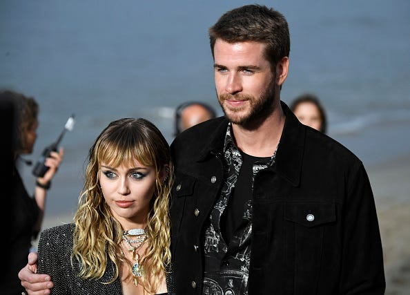 Exes Miley Cyrus and Liam Hemsworth pose for photos.