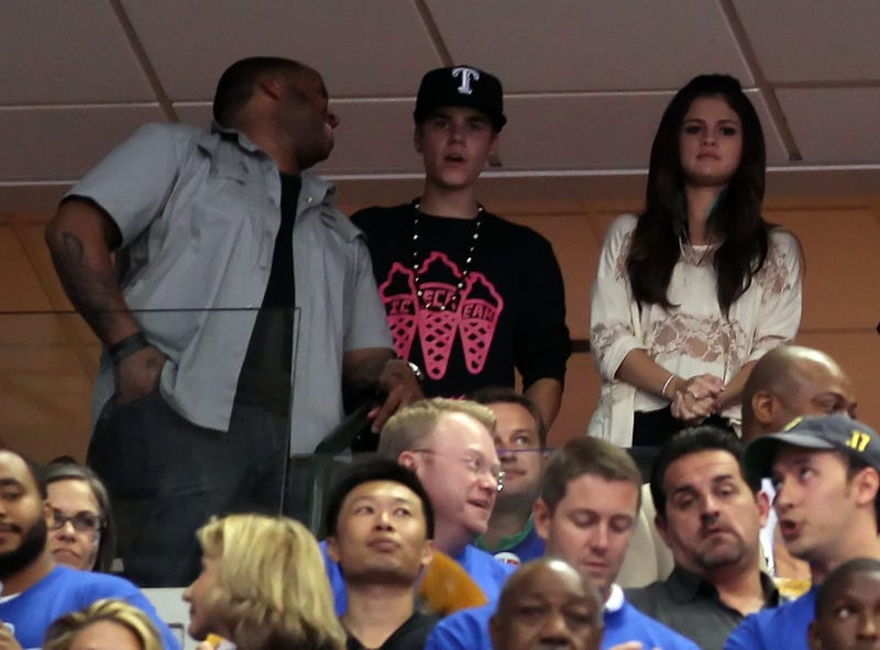 Kenny Hamilton and singers Justin Bieber and Selena Gomez attend Game Four of the 2011 NBA Finals