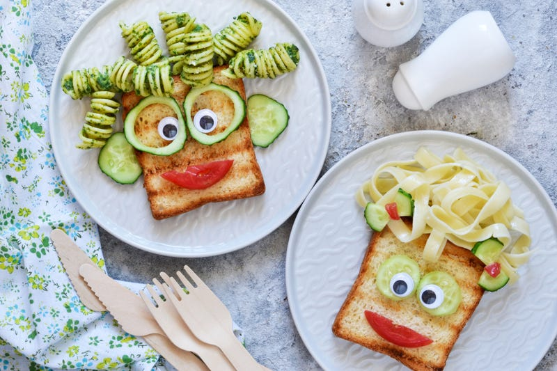 Lunch for children. Pasta with sandwiches and vegetables. Cheerful face.