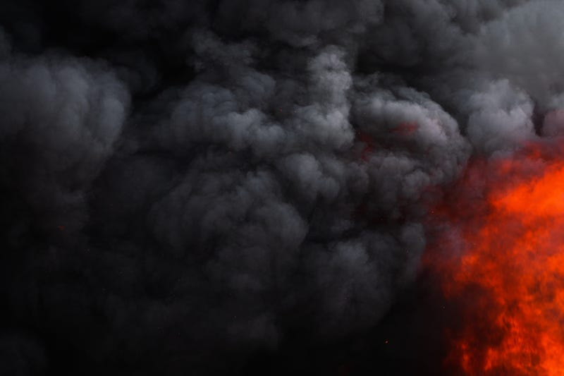 Dangerous red flames of strong fire and dramatic black clouds of smoke.