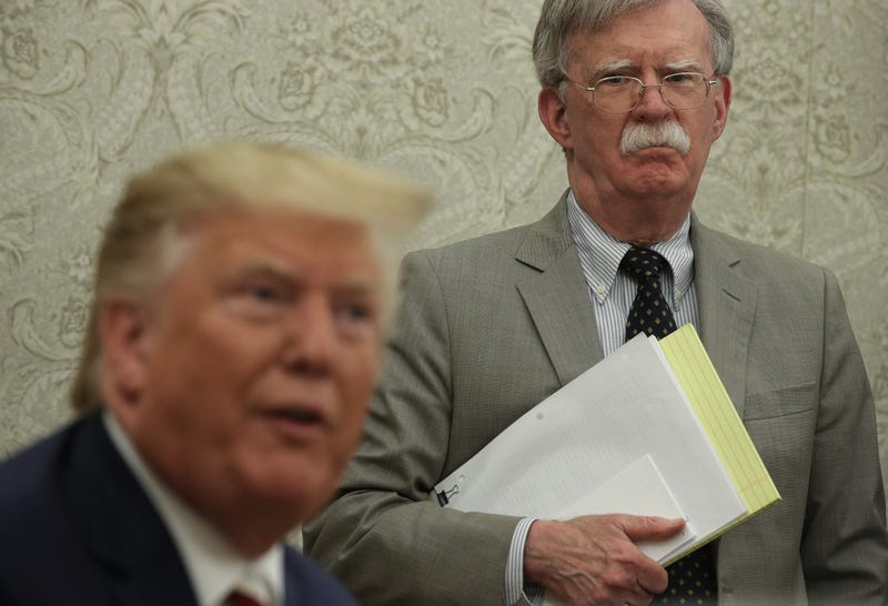 President Donald Trump speaks to members of the media as National Security Adviser John Bolton listens during a meeting with President of Romania Klaus Iohannis in the Oval Office of the White House August 20, 2019 in Washington, DC.