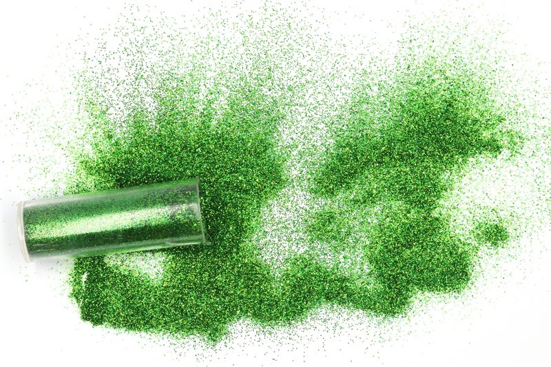 Jar with spilled green glitter Magical, celestial green glitter spilling out of a jar isolated on white background
