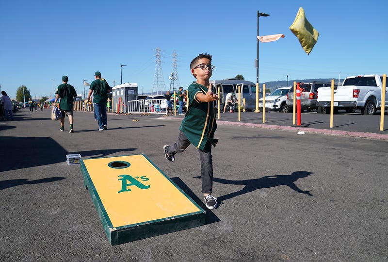 A young Oakland Athletics fan playing the game corn hole in the parking lot prior to the start of the American League WildCard Game against the Tampa Bay Rays at RingCentral Coliseum on October 2, 2019 in Oakland, California.