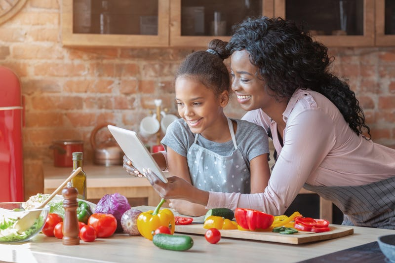 mother and daughter take online cooking class
