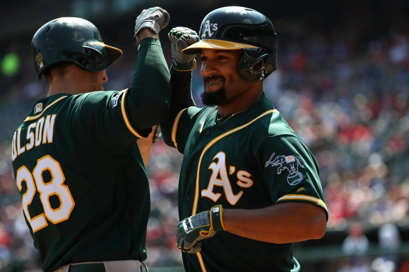 Marcus Semien bumps elbows with teammate Matt Olson
