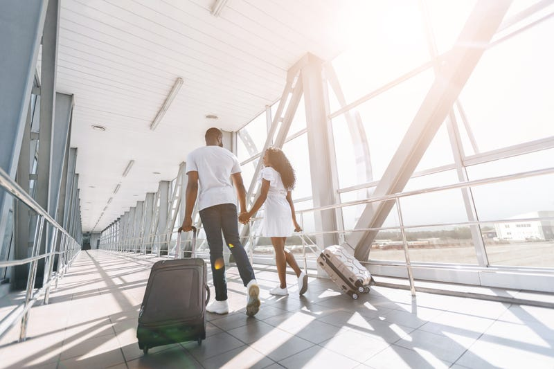 couple walking through the airport with luggage