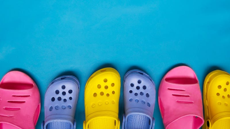 Brightly colored crocs on blue backgroound
