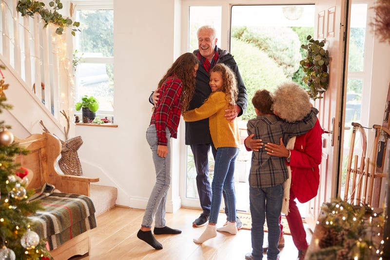 An older couple greet three children in a house decorated for Christmas