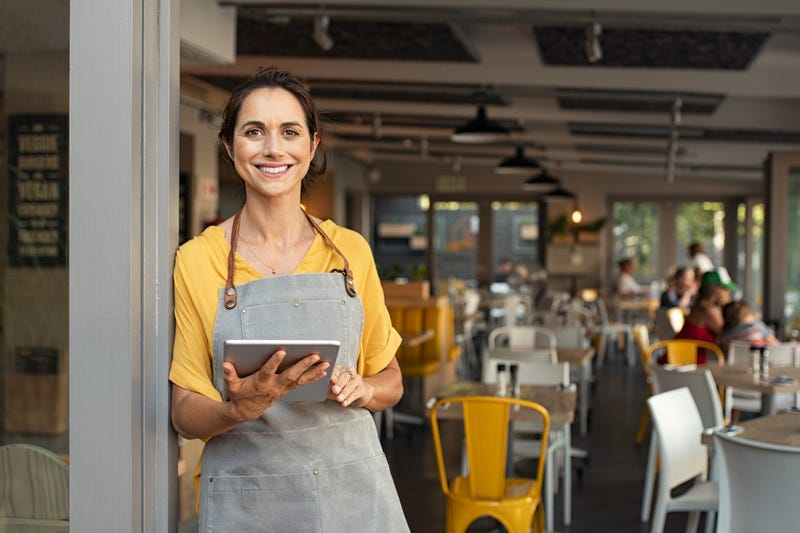 A woman stands in the doorway of a restaurant with a tablet