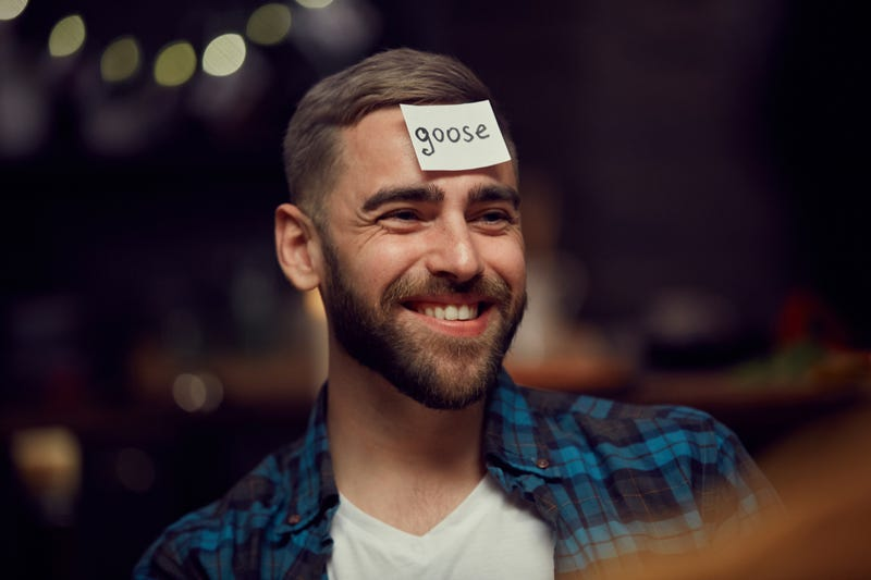 A man with a card on his forehead reading Goose