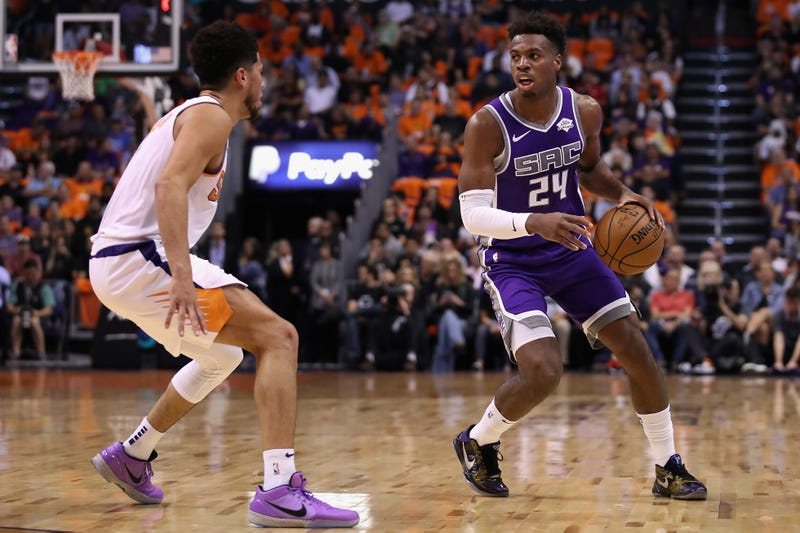 Devin Booker defends Buddy Hield on the perimeter.