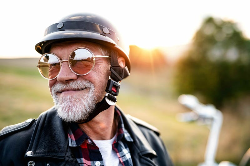 An old man in mirrored sunglasses and a helmet stands in front of a motorcycle