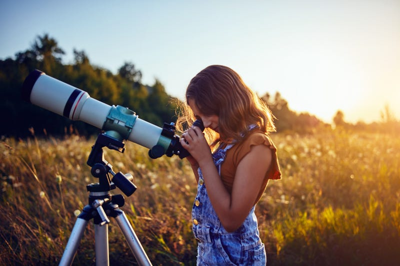 Little girl using telescope