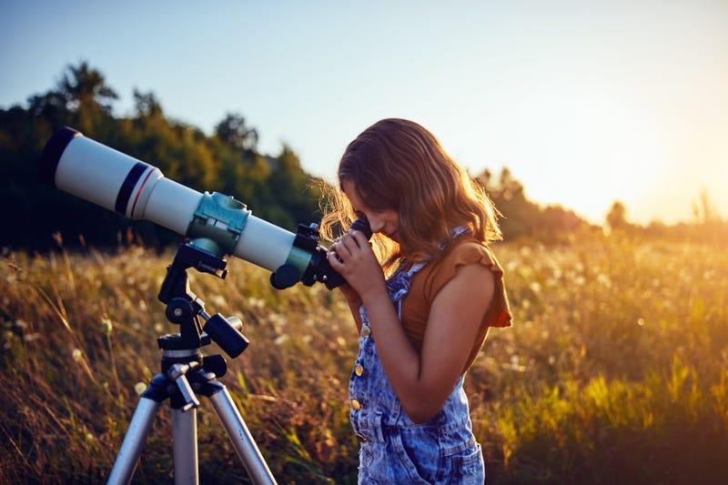 Little girl using telescope