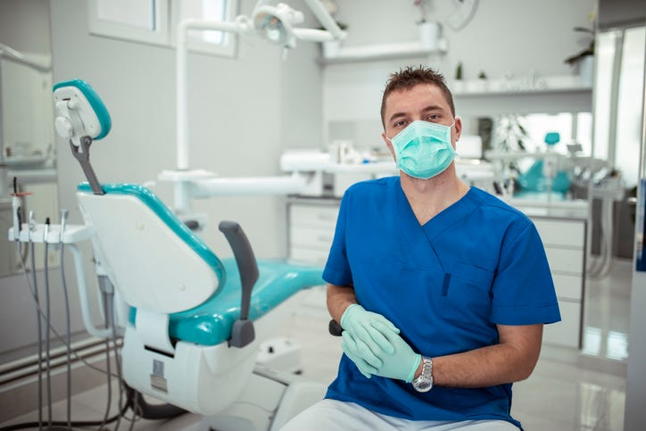dentist with surgical mask sitting in office