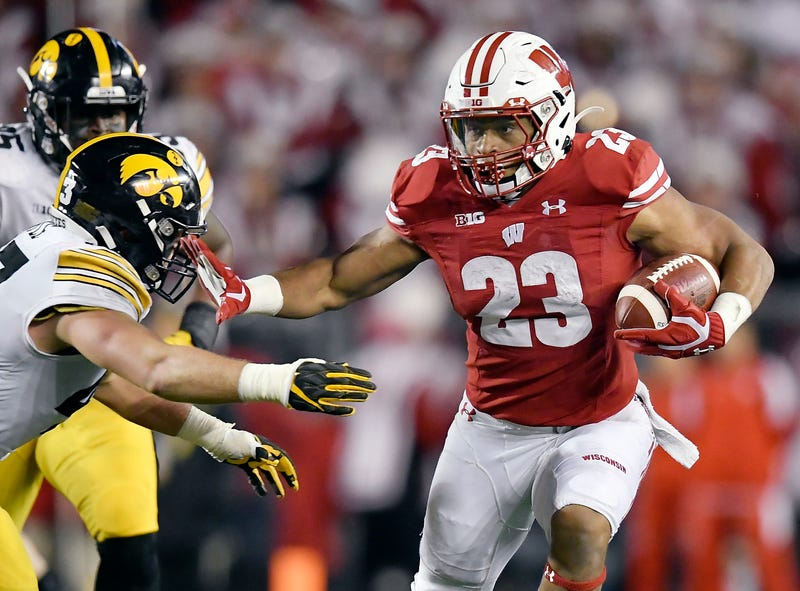 Wisconsin's Jonathan Taylor stiff-arms a defender