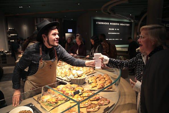 A Starbucks barista hands a customer a coffee.