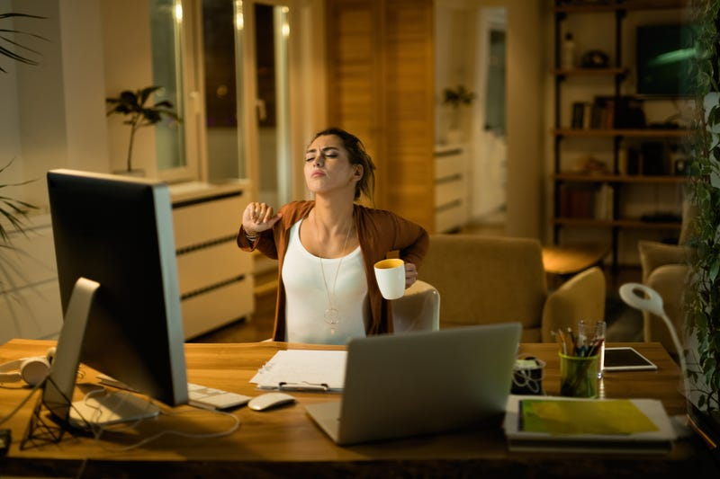A woman sitting at a home computer stretches her back