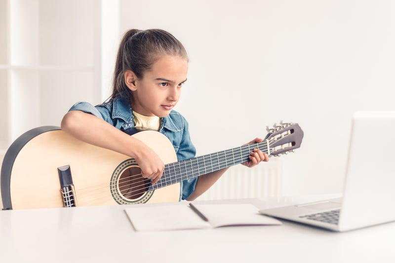 little girl taking guitar lesson online