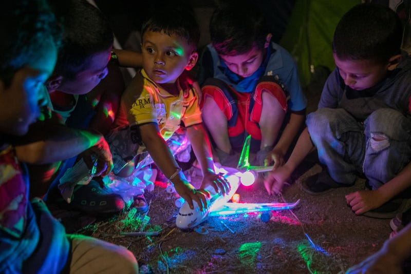 Honduran asylum seeker Michael, 2, secures his birthday present from fellow boys at an immigrant camp on December 08, 2019 in the border town of Matamoros, Mexico.