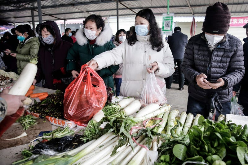Residents wear masks to buy vegetables in the market on January 23, 2020 in Wuhan, Hubei, China. Flights, trains and public transport including buses, subway and ferry services have been temporarily closed and officials have asked residents told to stay in town in order to help stop the outbreak of a strain of coronavirus