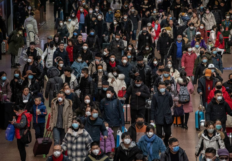 Chinese passengers, most wearing masks, arrive to board trains before the annual Spring Festival at a Beijing railway station on January 23, 2020 in Beijing, China. The number of cases of a deadly new coronavirus rose to over 500 in mainland China Wednesday as health officials locked down the city of Wuhan in an effort to contain the spread of the pneumonia-like disease.