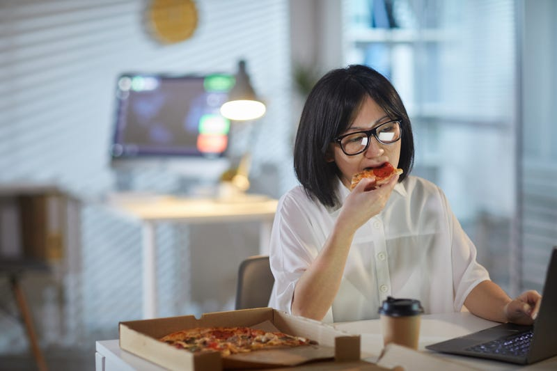 A woman eats pizza in front of a computer