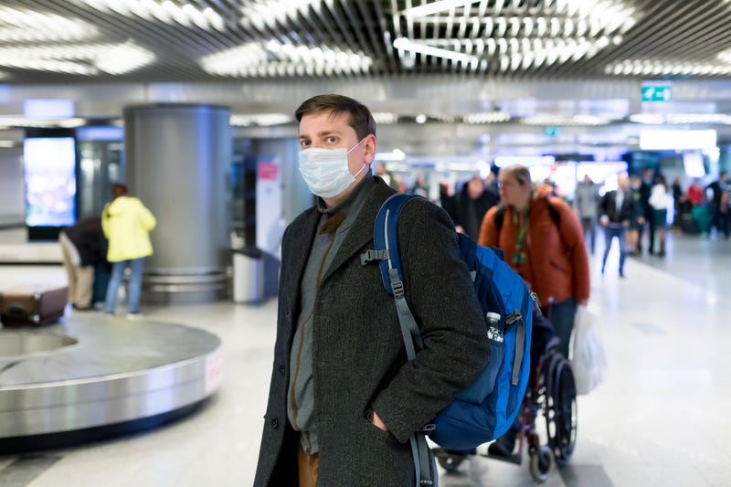 A man wearing a medical face mask in an airport