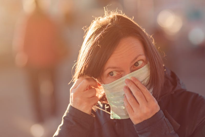 A woman in public puts on a medical face mask