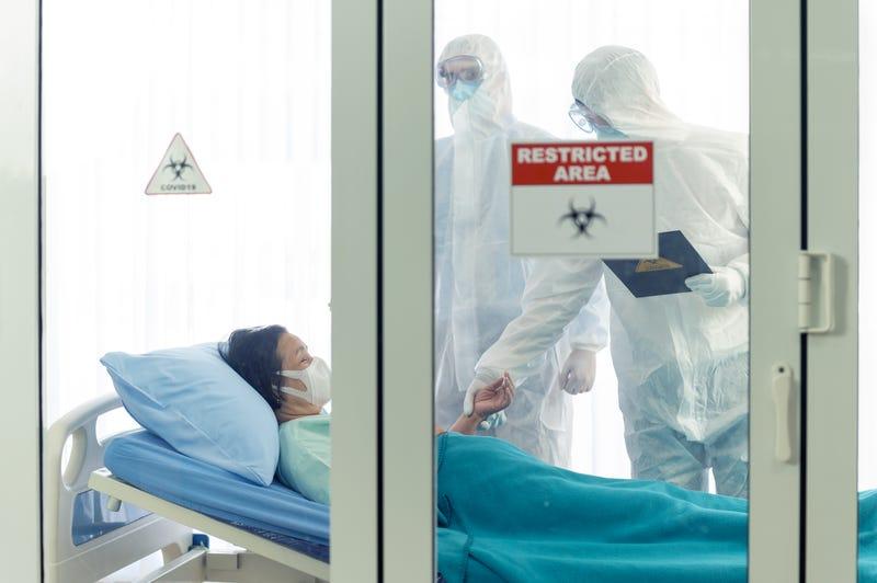 Doctors in hazmat suits inspect a sick patient in a quarantine area