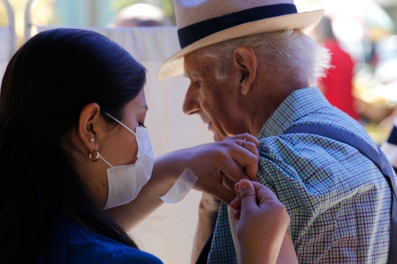 A nurse vaccinates a senior