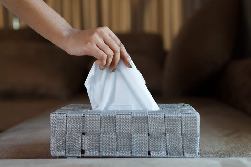A woman's hand takes a tissue from a box