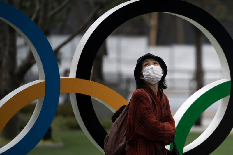 A woman wearing a face mask walks past the Olympic rings in front of the new National Stadium, the main stadium for the upcoming Tokyo 2020 Olympic and Paralympic Games