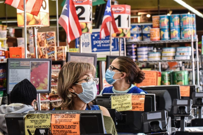 Cashiers wearing protective masks work in a grocery store in the Bushwick neighborhood of Brooklyn