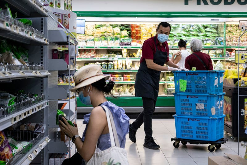 People wearing protective masks shop in a supermarket on April 6, 2020 in Singapore, a day before a 'circuit breaker' takes effect. The Singapore government will close all schools and most workplaces and limit social interactions and movement outside homes for at least a month to stem the spike in local coronavirus cases.