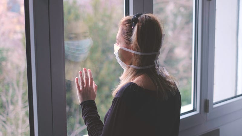 A woman in a medical mask looks longingly out a window